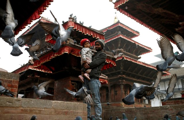 A family look at pigeons as they pass time at a temple in Kathmandu, Nepal on February 16, 2020. (Photo by Soe Zeya Tun/Reuters)