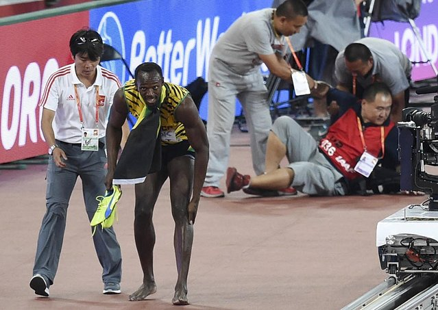 Usain Bolt of Jamaica (2nd L) rubs his feet after being hit by a cameraman (R) on a Segway after winning the men's 200 metres final at the 15th IAAF World Championships at the National Stadium in Beijing, China, August 27, 2015. (Photo by Reuters/Stringer)