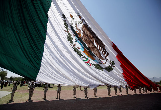 Soldiers hold a giant national flag as it raised during preparations for the 207th anniversary of Mexico's independence from Spain, to be celebrated on September 16, in Ciudad Juarez, Mexico September 4, 2017. (Photo by Jose Luis Gonzalez/Reuters)