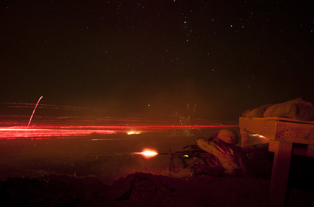 Pfcs. Greg Zecher and Nicholas Roberts, machine gunners with Lima Company, 3rd Battalion, 3rd Marine Regiment, illuminate the night sky by firing tracer rounds and then reloading their weapons during Exercise Clear, Hold, Build 3 on Marine Corps Air Ground Combat Center Twentynine Palms, Calif., September 21, 2011. (Photo by Cpl. Reece Lodder/Marine Corps Base Hawaii)