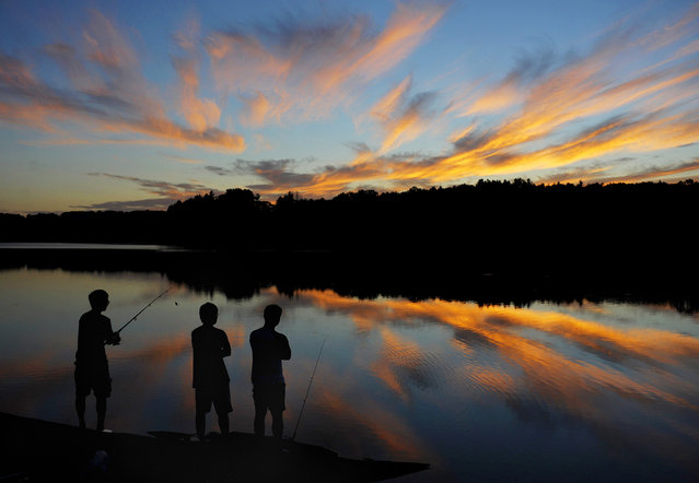 UConn students from Storrs, Conn., Gary Tu, Danny Wang and Victor Zheng, fish at Shenipsit Lake in Tolland, Conn. during sunset on Tuesday, August 19, 2014. (Photo by Jim Michaud/AP Photo/Journal Inquirer)