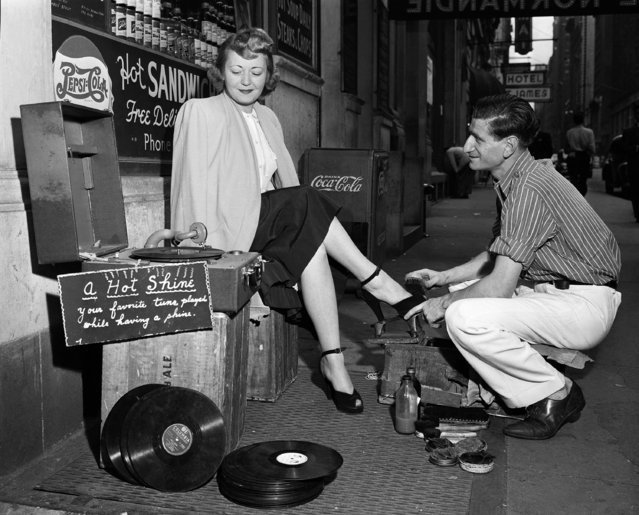 """Music-minded Jack Rosenberg, right, shines shoes while his appreciative customer listens to his records near Times Square, New York, August 18, 1948. Jack claims to be the world's first disc jockey shoe shine boy. """"You'd be surprised how it helps with the tips"""" said Jack. (Photo by Ed Ford/AP Photo)"""