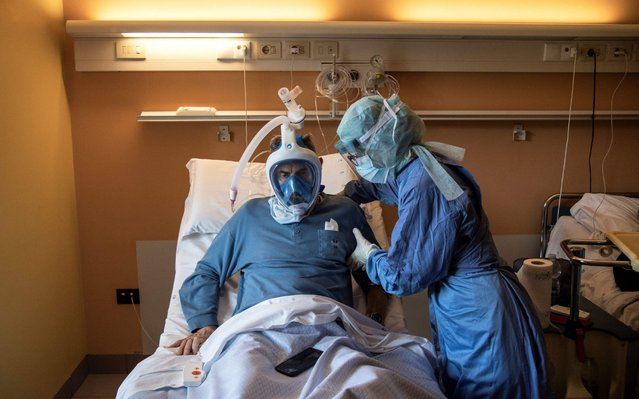 A nurse helps a patient suffering from COVID-19 who uses the Decathlon snorkeling face mask in the COVID ward of the Maria Pia Hospital in Turin on April 7, 2020. This private facility converted into a COVID hospital is the first to use snorkeling mask from Decathlon as CPAP (Continuous Positive Airway Pressure) for patients suffering from novel coronavirus (COVID-19). (Photo by Marco Bertorello/AFP Photo)