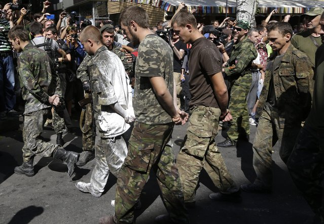 Pro-Russian rebels escort prisoners of war from the Ukrainian army in a central square in Donetsk, eastern Ukraine, Sunday, August 24, 2014. Ukraine has retaken control of much of its eastern territory bordering Russia in the last few weeks, but fierce fighting for the rebel-held cities of Donetsk and Luhansk persists. (Photo by Sergei Grits/AP Photo)