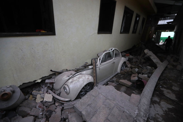 A car sits crushed from a building felled by a 7.1 earthquake, in Jojutla, Morelos state, Mexico, Wednesday, September 20, 2017. Efforts continue at the scenes of dozens of collapsed buildings, where firefighters, police, soldiers and civilians continue their search to reach the living. (Photo by Eduardo Verdugo/AP Photo)