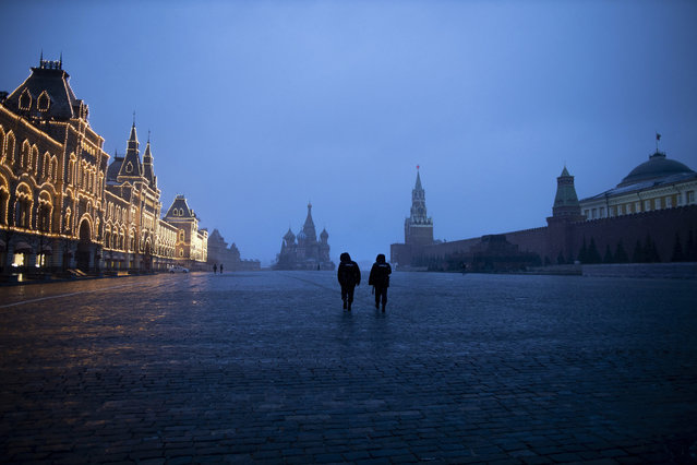 Two police officers patrol an almost empty Red Square, with St. Basil's Cathedral, center, and Spasskaya Tower and the Kremlin Wall, right, at the time when its usually very crowded in Moscow, Russia, Monday, March 30, 2020. Russian President Vladimir Putin says the country has managed to slow down the spread of coronavirus but should be prepared for contagions to quickly grow. (Photo by Alexander Zemlianichenko/AP Photo)