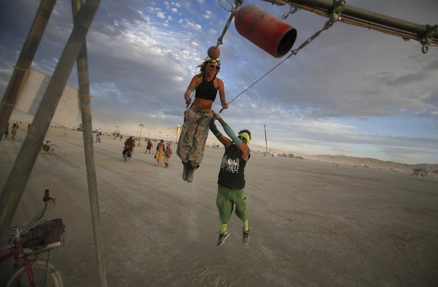 "Gwen Barker (L) and Rezwan Khan play on a swing art installation during the Burning Man 2014 ""Caravansary"" arts and music festival in the Black Rock Desert of Nevada, August 30, 2014. (Photo by Jim Urquhart/Reuters)"