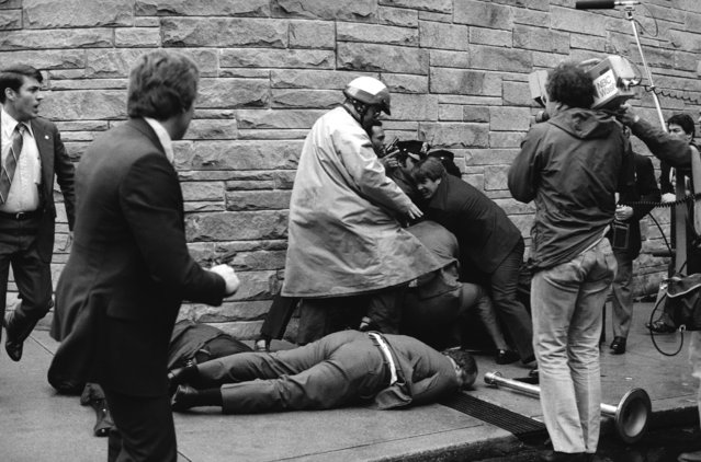 Secret Service agent Timothy J. McCarthy, foreground, Washington policeman, Thomas K. Delehanty, center, and presidential Press Secretary, James Brady, background, lie wounded on a street outside a Washington hotel after shots were fired at U.S. President Reagan on March 30, 1981. (Photo by Ron Edmonds/AP Photo)