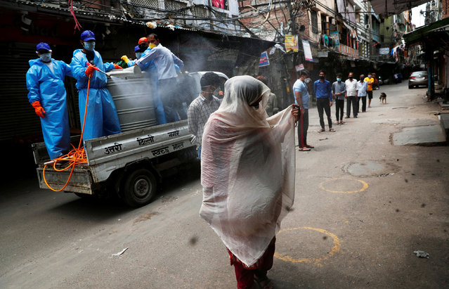 Municipal workers spray disinfectant on the people stand in a queue next to a mobile test station for coronavirus disease (COVID-19) at a residential area in the old quarters of Delhi, India, April 20, 2020. (Photo by Adnan Abidi/Reuters)