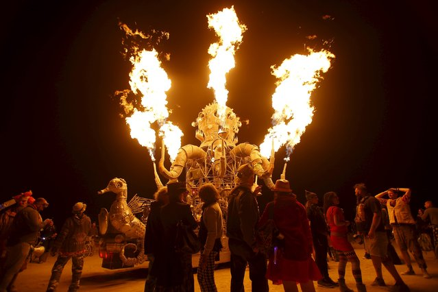 "Participants gather to watch the flames from the art car El Popo Mechanico during the Burning Man 2015 ""Carnival of Mirrors"" arts and music festival in the Black Rock Desert of Nevada, September 3, 2015. (Photo by Jim Urquhart/Reuters)"
