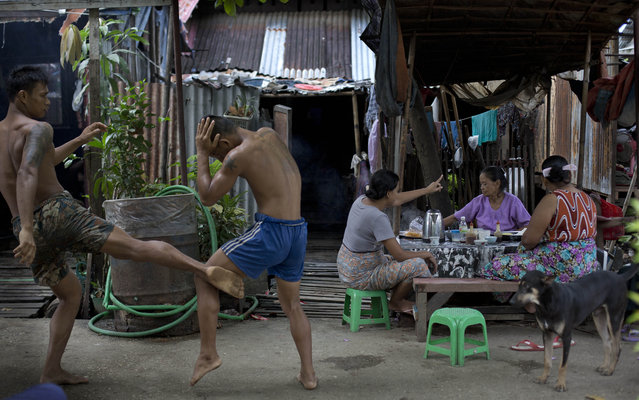 In this Wednesday, July 15, 2015, photo, a member of the White New Blood lethwei fighters club, a Myanmar traditional martial-arts club which practices a rough form of kickboxing,  practice in their gym on a street as customers eat a meal at a roadside noodles shop in Oakalarpa, north of Yangon, Myanmar. (Photo by Gemunu Amarasinghe/AP Photo)