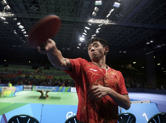 2016 Rio Olympics, Table Tennis, Men's Team, Semifinals, Riocentro, Pavilion 3, Rio de Janeiro, Brazil on August 16, 2016. Zhang Jike (CHN) of China uses a paddle to lob balls into the audience after winning their match against South Korea. (Photo by Alkis Konstantinidis/Reuters)