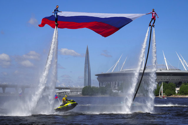 Members of the Russian hydroflight team hold the Russian national flag during the Day of Russia celebration in St.Petersburg, Russia, Friday, June 12, 2020, with business tower Lakhta Centre, the headquarters of Russian gas monopoly Gazprom and Gazprom Arena soccer stadium in the background. (Photo by Dmitri Lovetsky/AP Photo)
