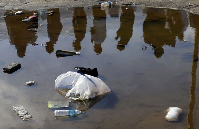 "Migrants are reflected in a puddle as they wait for the distribution of food at the makeshift camp called ""The New Jungle"" in Calais, France, September 19, 2015. (Photo by Regis Duvignau/Reuters)"