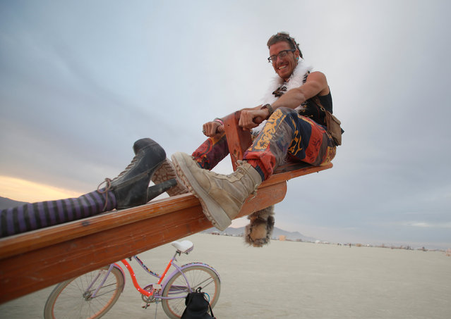 A participant rides a teeter-totter as approximately 70,000 people from all over the world gather for the 30th annual Burning Man arts and music festival in the Black Rock Desert of Nevada, U.S. August 30, 2016. (Photo by Jim Urquhart/Reuters)