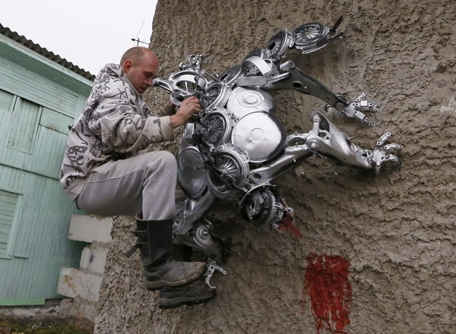 Mechanic and welder Sergei Kulagin, 32, strengthens the bracing of a spider sculpture, made by Kulagin, during a demonstration on the wall of an automobile repair workshop in the town of Divnogorsk outside Krasnoyarsk, Siberia, October 15, 2014. Enthusiast Kulagin, who works as a mechanic of an automobile service station, created about 20 sculptures made of used car parts and components during his non-working hours. (Photo by Ilya Naymushin/Reuters)