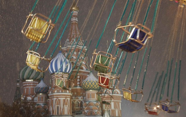 A merry-go-round turns in front of St. Basil's Cathedral in Red Square in Moscow, Russia December 5, 2017. (Photo by Grigory Dukor/Reuters)