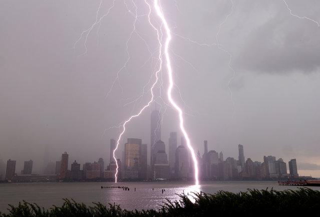 Two lightning bolts frame One World Trade Center as they hit the Hudson River in front of the skyline of lower Manhattan in New York City during a thunderstorm on July 6, 2020 as seen from Jersey City, New Jersey. (Photo by Gary Hershorn/Getty Images)