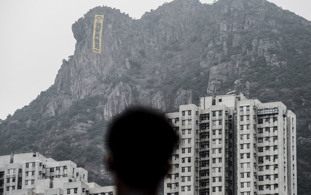A man looks at a large pro-democracy banner displayed on the Lion Rock Hill in Hong Kong on October 23, 2014. Major intersections in the southern Chinese city have been paralysed by mass rallies demanding free elections for more than three weeks, in one of the biggest challenges to Beijing's authority since the Tiananmen pro-democracy protests of 1989. (Photo by Philippe Lopez/AFP Photo)
