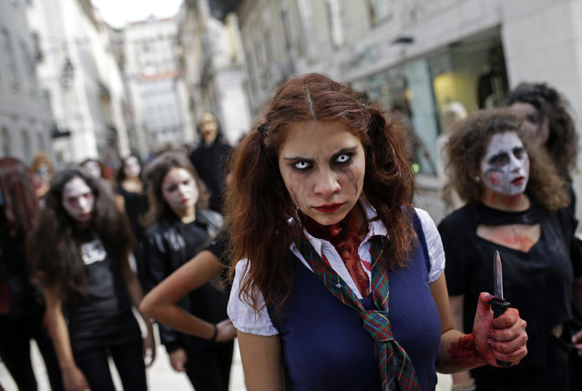 A group of youngsters dressed as ghouls and zombies for Halloween parade in downtown Lisbon, Portugal, Friday, October 31, 2014. (Photo by Francisco Seco/AP Photo)