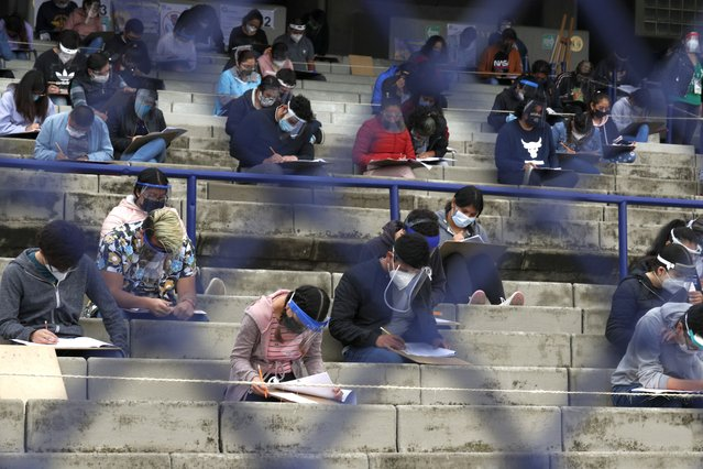 Prospective students are seen through a fence in the stands of University Olympic Stadium where they take the entrance exam for Mexico's National Autonomous University, amidst the ongoing coronavirus pandemic in Mexico City, Wednesday, August 19, 2020. More than 2,000 hopefuls registered to take the exam at the stadium, where it was being offered for the first time, and more than 80,000 aspirants were registered nationwide to take the exam. (Photo by Rebecca Blackwell/AP Photo)