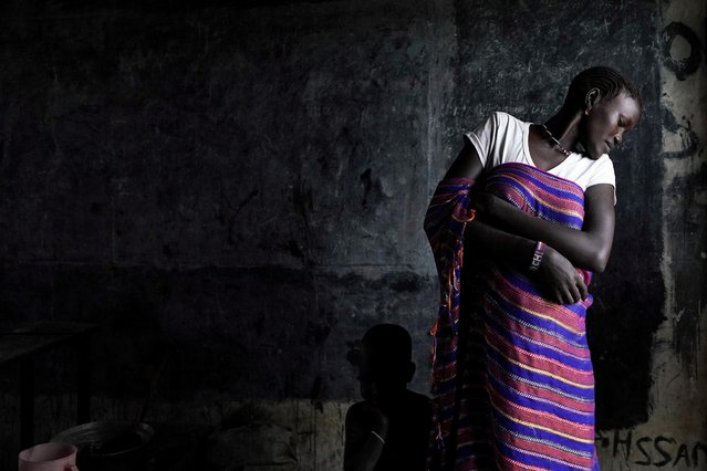 A displaced woman looks at her child who is hiding behind her dress, in a school now occupied by IDPs (Internally Displaced People) after heavy rains and floods forced hundreds of thousands of people to leave their homes, in the town of Pibor, Boma state, South Sudan, November 6, 2019. (Photo by Andreea Campeanu/Reuters)