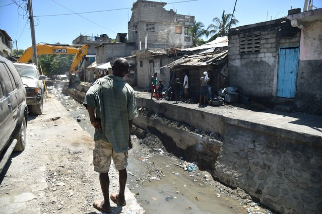A man watches while a bulldozer clean debris in a canal, in Cap-Haitien, on September 6, 2017, 240 km from Port-au-Prince, in preparation before the arrival of Hurricane Irma. Some people in Cap-Haitien still do not have information on the arrival of Hurricane Irma and many others do not know what to do or where to go to take shelter. (Photo by Hector Retamal/AFP Photo)