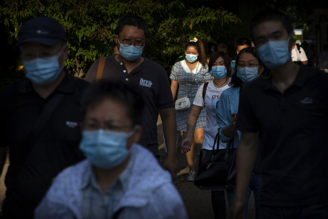 People wearing face masks to protect against the coronavirus walk along a street in the central business district in Beijing, Wednesday, September 2, 2020. Even as China has largely controlled the outbreak, the coronavirus is still surging across parts of the world. (Photo by Mark Schiefelbein/AP Photo)
