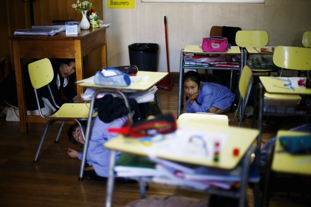 A teacher and her students take cover under their desk inside a school during an earthquake drill in Santiago, November 13, 2014. (Photo by Ivan Alvarado/Reuters)