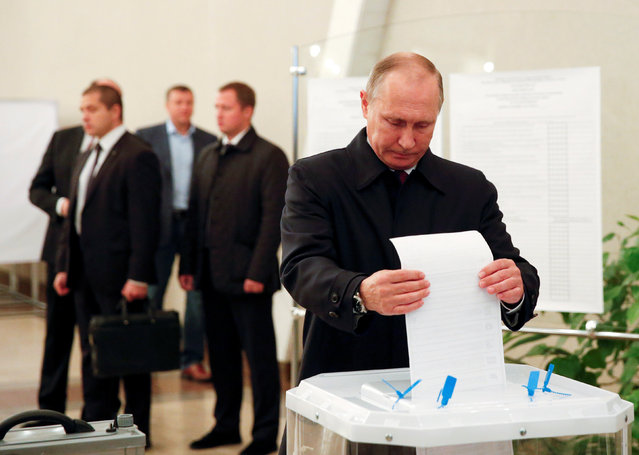 Russian President Vladimir Putin casts his ballot at a polling station during a parliamentary election in Moscow, Russia, September 18, 2016. The ruling United Russia party is expected to win even greater dominance over Russia's parliament in an election on Sunday, showing that support for President Vladimir Putin is holding up despite sanctions and a deep economic slowdown. The party is able to draw on the support of the other three parties in the federal Duma, and benefits from its association with 63-year-old Putin, who after 17 years in power as either president or prime minister, enjoys a personal approval rating of about 80 percent. Putin does not belong to any party. By contrast, liberal opposition politicians, who have just one sympathetic member in the Duma, complain they are starved of air time, vilified by state media, and their campaigns systematically disrupted by pro-Kremlin provocateurs. Pro-Kremlin politicians deny that charge. (Photo by Grigory Dukor/Reuters)