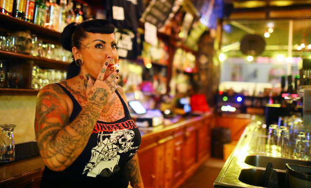 Petra, who works behind the bar, smokes at Trinkteufel pub in Berlin, Germany, August 31, 2016. Trinkteufel is open from Friday to Monday morning, non-stop. It attracts anyone from old punks, to tourists, to artists, to retirees. (Photo by Hannibal Hanschke/Reuters)