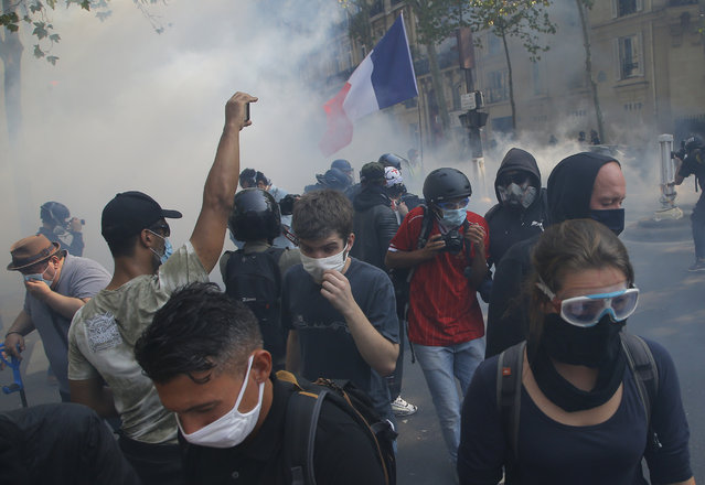 Yellow vest protesters escape tear gas fired by French police while wearing protective face masks as precaution against the conoravirus during a march in Paris, Saturday, September 12, 2020. (Photo by Michel Euler/AP Photo)