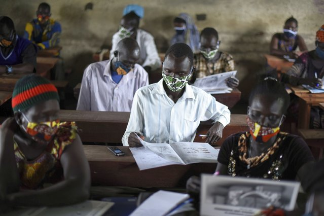 """A trainee reads a handbook on coronavirus prevention, at a training session for community health workers conducted by the national NGO """"Health Link"""" in Gumbo, on the outskirts of Juba, South Sudan, Tuesday, August 18, 2020. The coronavirus is exposing an uncomfortable inequality in the billion-dollar system that delivers life-saving aid to countries in crisis: Most money goes to international aid groups instead of local ones and now many local aid workers have been left exposed on the pandemic's front lines. (Photo by Charles Atiki Lomodong/AP Photo)"""