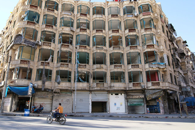 A man rides a motorcycle past a damaged building in the rebel-held al-Shaar neighbourhood of Aleppo, Syria, September 17, 2016. (Photo by Abdalrhman Ismail/Reuters)