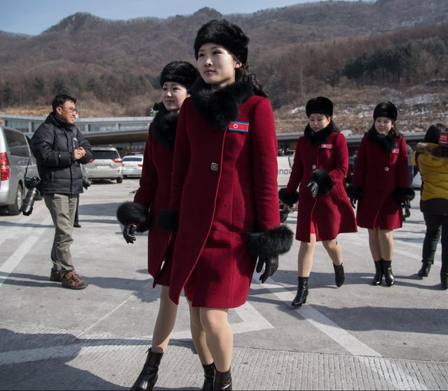 North Korean cheerleaders arrive at a rest stop, or service station, as their bus convoy carrying a 280- member delegation on its way to the 2018 Pyeongchang winter Olympic games, makes its way past Gapyeong on February 7, 2018 More than 200 young North Korean women arrived in South Korea to root for athletes from both sides of the peninsula at the Winter Olympics. (Photo by Ed Jones/AFP Photo)