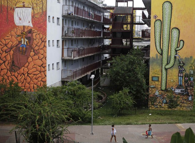 Residents walk past drought-related murals on buildings in Sao Paulo November 25, 2014. The murals, painted by Brazilian artists Mundano and Fel, depict a boat on a cracked riverbed (L) and a man getting water from a cactus (R). Brazil's worst drought in 80 years has left the Cantareira system, which provides greater Sao Paulo with most of its water, with the lowest water level on record. (Photo by Nacho Doce/Reuters)