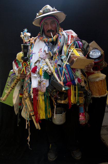 "In this February 6, 2018 photo, Juan Ricaldi, dressed as ""Ekeko"", the god of prosperity, is covered in objects including instruments as he holds a cigarette in his mouth during a portrait session on the sidelines of the annual Alasita Fair in La Paz, Bolivia. ""For me, the Ekeko hasn't made me rich but allows me to live"", said the 59-year-old artisan. ""I can say that the Ekeko has made my dreams come true, has never left me and will be with me forever"", he said. Ricaldi won this year's Ekeko competition. (Photo by Juan Karita/AP Photo)"