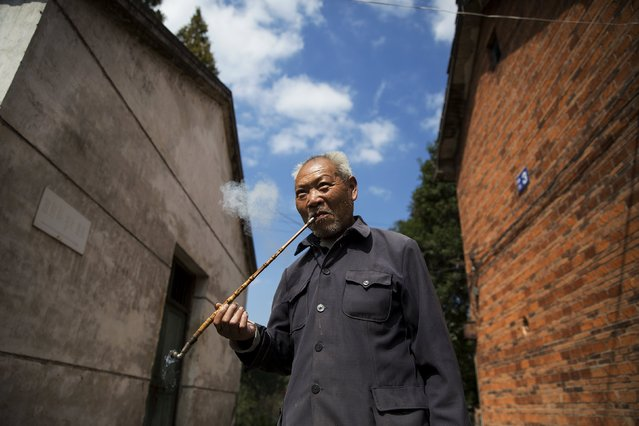 Wang Zhengqing, a 74 year old pneumoconiosis patient, smokes his pipe at Yangjia Hospital in Wuyi County, Zhejiang Province, China October 19, 2015. Former miner Wang was diagnosed with the disease, which is caused by dust inhalation, when he was 24 and has lived at Yangjia Hospital for ten years. (Photo by Damir Sagolj/Reuters)