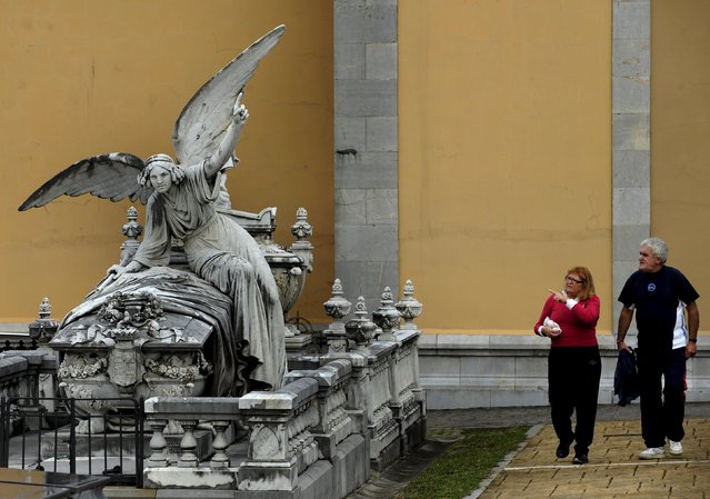 A couple walks near the pantheon of the Marquesa de San Juan de Nieva, chosen as the best tomb sculpture of Spain in a Spanish magazine this week, in the municipal cemetery of La Carriona in Aviles, northern Spain, October 29, 2015. (Photo by Eloy Alonso/Reuters)
