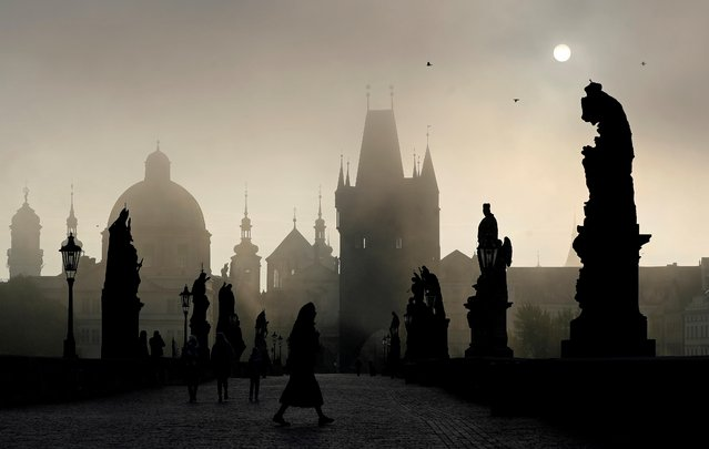 People walk across the medieval Charles Bridge as the sun rises in Prague, Czech Republic, October 1, 2020. (Photo by David W. Cerny/Reuters)