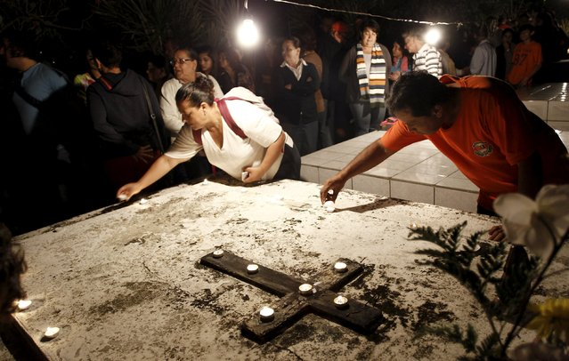 People place candles on the grave as they take part in a vigil at a cemetery in Barva de Heredia, Costa Rica October 31, 2015. (Photo by Juan Carlos Ulate/Reuters)