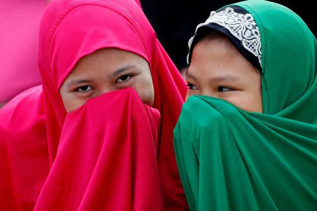 Filipino Muslims cover their faces as they gather outside the Blue Mosque to pray in celebration of Eid al-Fitr Friday, June 15, 2018 at the Blue Mosque in suburban Taguig city, east of Manila, Philippines. Muslims all over the world mark Eid al-Fitr with prayers, family reunions and gift-givings. (Photo by Bullit Marquez/AP Photo)
