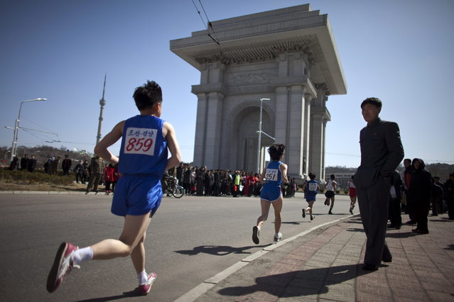 People watch marathon runners near the Arch of Triumph in Pyongyang, North Korea, Sunday, April 14, 2013. North Koreans held the 26th Mangyongdae Prize Marathon to mark the upcoming birthday of the late leader Kim Il Sung on April 15. (Photo by Alexander F. Yuan/AP Photo)