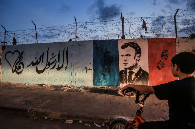 A mural on a wall shows French President Macron and the French flag with shoe prints in protest against Macron's latest comments about Islam in Gaza Strip on October 28, 2020. (Photo by Abed Alrahman Alkahlout/Quds Net News/ZUMA Wire/Rex Features/Shutterstock)
