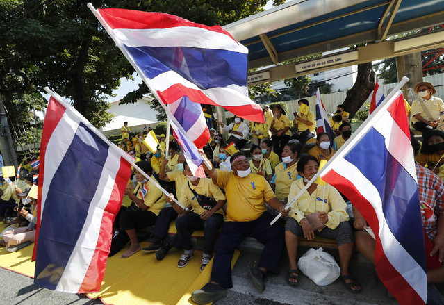 Supporters of the Thai monarchy wave nation flag as they gather near the parliament in Bangkok, Thailand, Tuesday, November 17, 2020. Thailand's political battleground shifted Tuesday to the country's Parliament, where lawmakers are considering proposals to amend the country's constitution, one of the core demands of the country's student-led pro-democracy movement. (Photo by Sakchai Lalit/AP Photo)