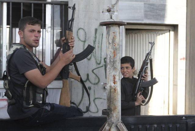 A Free Syrian Army fighter and a boy hold up weapons on a street at the Syrian town of Tel Abyad, near the border with Turkey, April 23, 2013. (Photo by Hamid Khatib/Reuters)