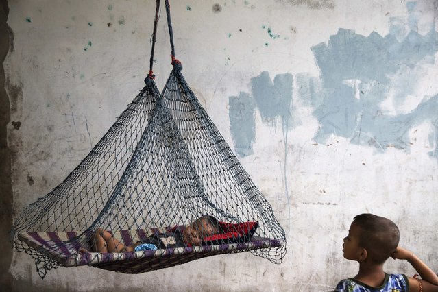 A son of a migrant fisherman from Myanmar rests in a hammock at a former shrimp warehouse where his family lives in Ban Nam Khem, December 13, 2014. (Photo by Damir Sagolj/Reuters)