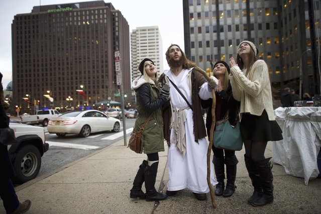 "Leah DeTommaso, 19, Alisyn Davidson, 19, and Taylor Moran, 18, ask to take a photograph with (center) Michael Grant, 28, ""Philly Jesus"", on December 14, 2014. (Photo by Mark Makela/Reuters)"