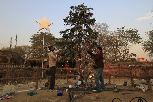 Men decorate a Christmas tree ahead of Christmas in a Christian slum in Islamabad December 23, 2014. (Photo by Faisal Mahmood/Reuters)