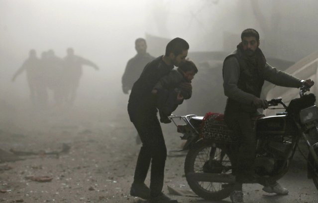 A man carries an injured child to a motorcycle at a site hit by what activists said was an air strike by forces of Syria's President Bashar al-Assad in the Duma neighbourhood of Damascus December 27, 2014. (Photo by Bassam Khabieh/Reuters)